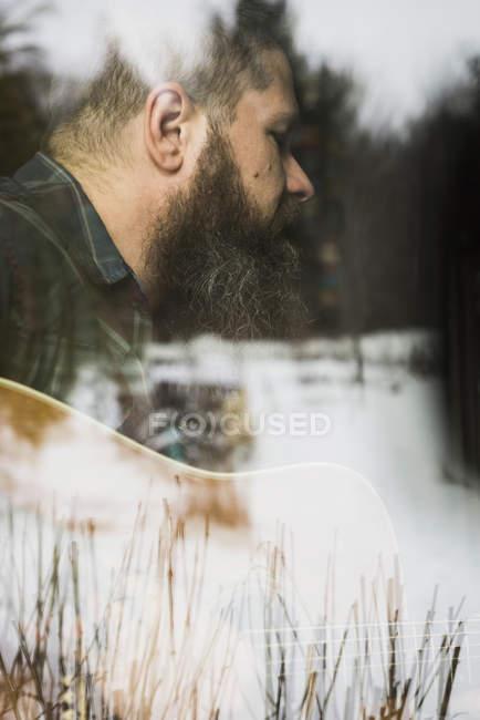 Bearded man playing guitar beside window — Stock Photo