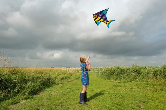 Fille cerf-volant volant dans le champ rural — Photo de stock