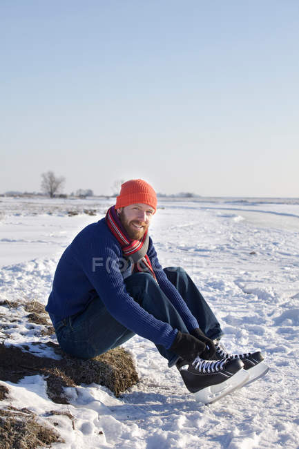 Man lacing up ice skates in snowy field — Stock Photo
