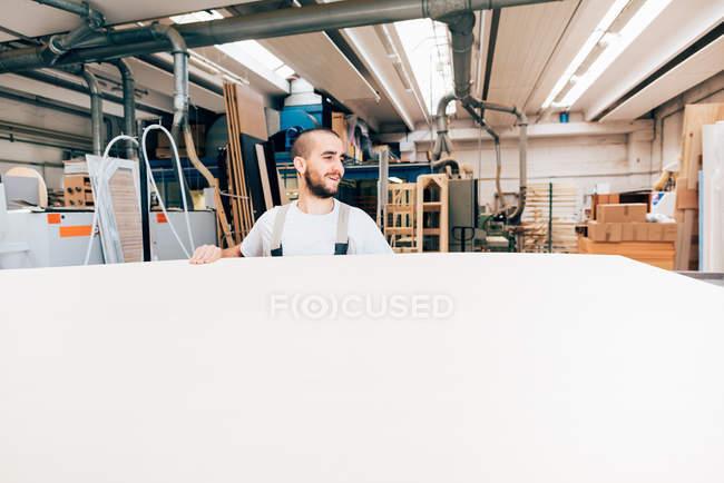 Menuisier avec grande feuille de bois en atelier — Photo de stock