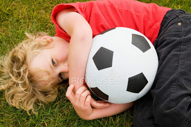 Хлопчик тримає футбольний м'яч у траві — стокове фото