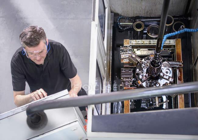Ingeniero en gafas de seguridad operando perforadora industrial - foto de stock