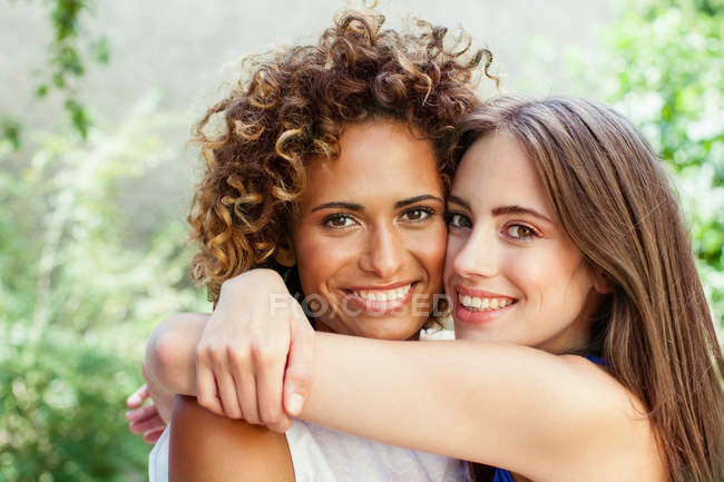 Smiling women hugging outdoors — Stock Photo