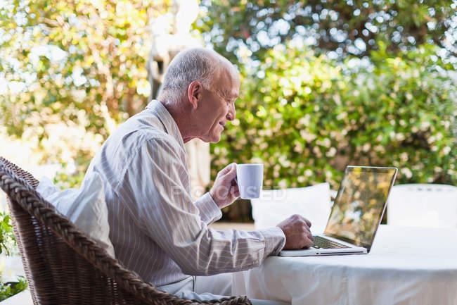 Uomo più anziano utilizzando il computer portatile all'aperto — Foto stock
