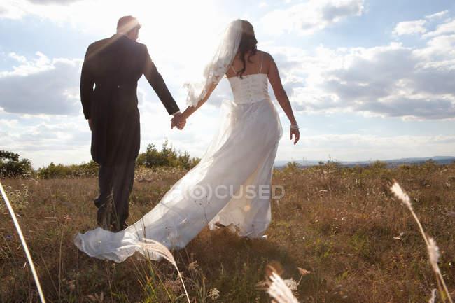 Молодая пара держится за руки в траве — стоковое фото