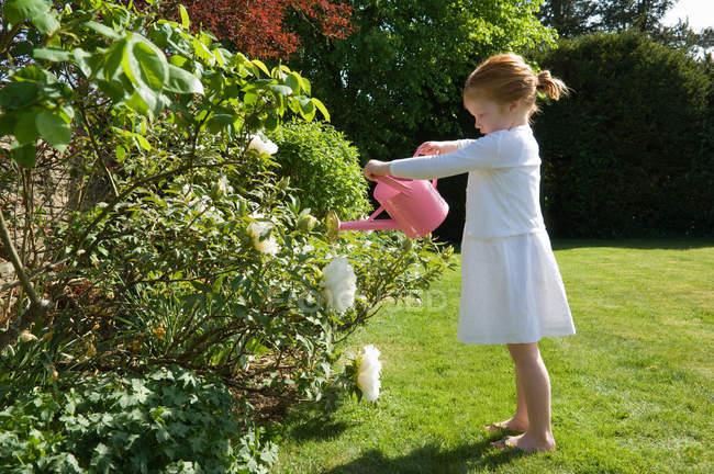 Flores de rega garota no quintal — Fotografia de Stock