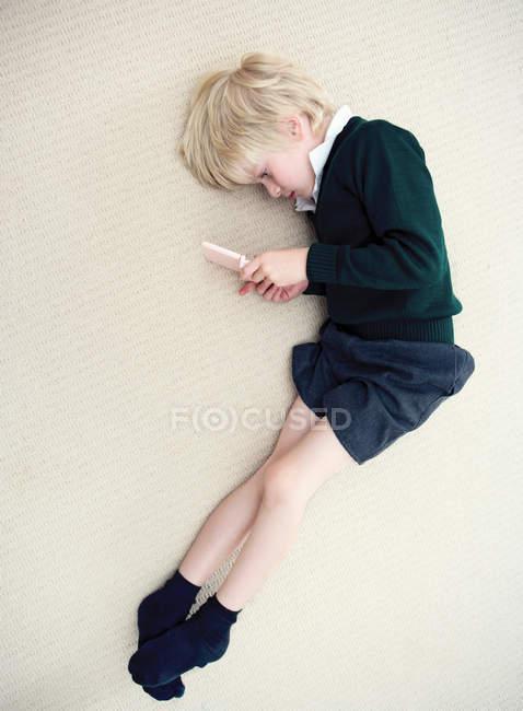 Boy lying on floor playing with nintendo — Stock Photo