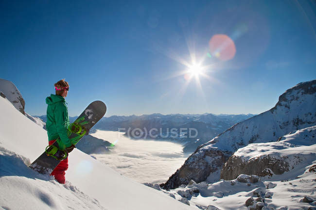 Snowboarder looking from mountain top — Stock Photo