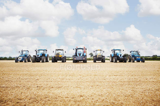Tractors harvesting grains — Stock Photo
