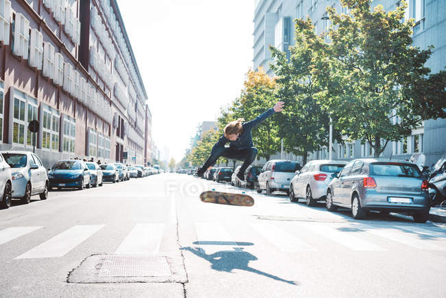 Young male urban skateboarder jumping mid air on pedestrian crossing — Stock Photo