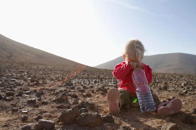 Малюк з пляшкою води в пустелі — стокове фото