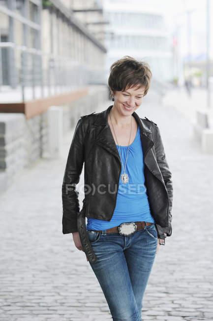 Donna sorridente che cammina sulla strada della città — Foto stock