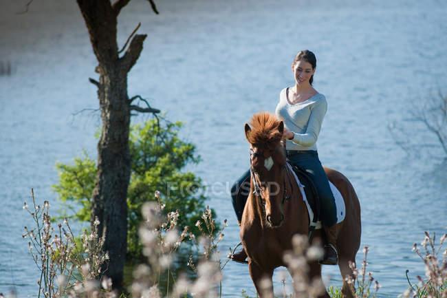 Mulher equitação cavalo pelo lago rural — Fotografia de Stock