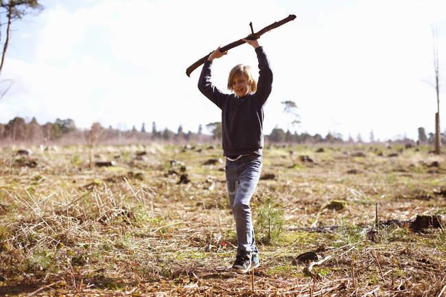 Junge hält auf einer Plantage einen Stock hoch — Stockfoto