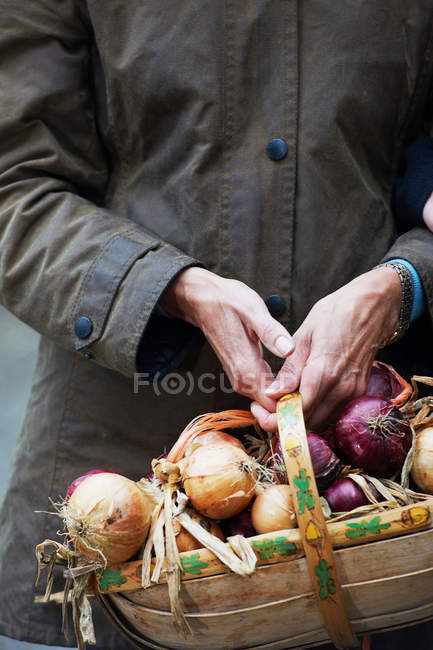 Grandmother holding basket of onions — Stock Photo