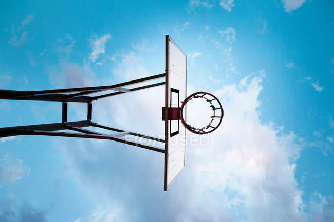 Basketball hoop under blue cloudy sky, low angle view — Stock Photo