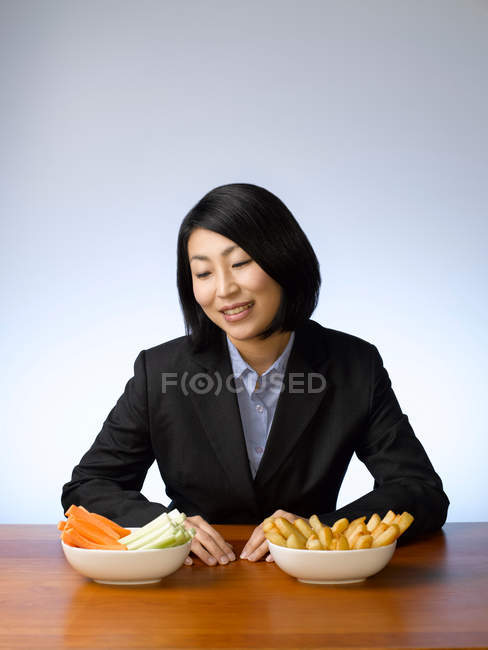 Businesswoman deciding what to eat, focus on foreground — Stock Photo