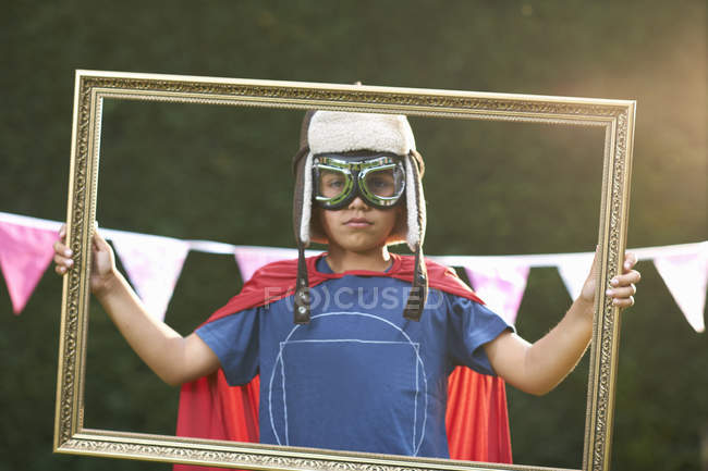 Portrait of boy looking through picture frame wearing cape, goggles and flying hat — Stock Photo