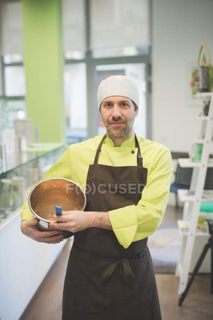 Baker carrying mixing bowl in cafe, looking in camera — Stock Photo
