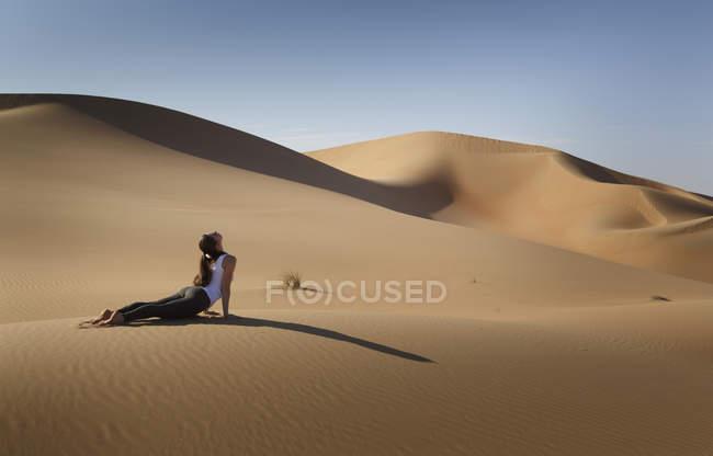 Mujer practicando yoga en una duna de arena en el desierto, Abu Dhabi, emirato de Abu Dhabi, Emiratos Árabes Unidos - foto de stock