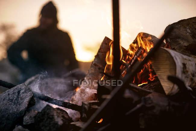 Nahaufnahme von Lagerfeuer am Sonnenuntergang, selektiven Fokus mit Person auf Hintergrund — Stockfoto