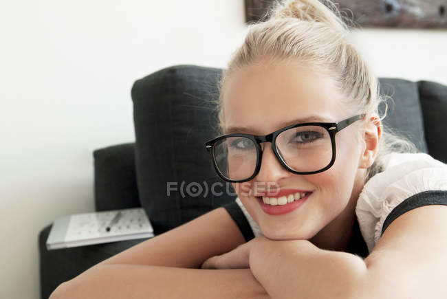 Ragazza adolescente sorridente sul divano — Foto stock