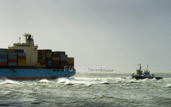 Container ship run aground with tugs rescuing — Stock Photo