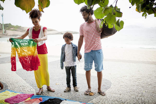 Couple and son choosing sweater from sidewalk stall, Ipanema beach, Rio De Janeiro, Brazil — Stock Photo
