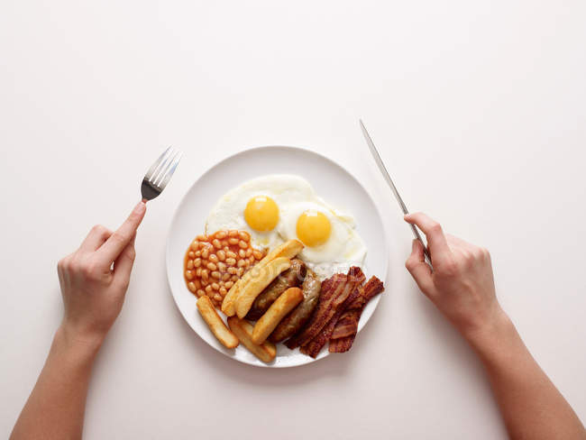 Hands by plate of fried breakfast — Stock Photo
