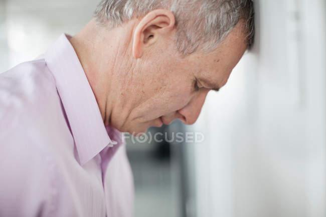 Front de penchement homme d'affaires sur mur — Photo de stock