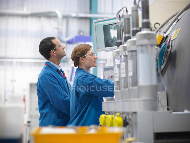 Male and female engineers or scientists work with vacuum tank in engineering factory — Stock Photo