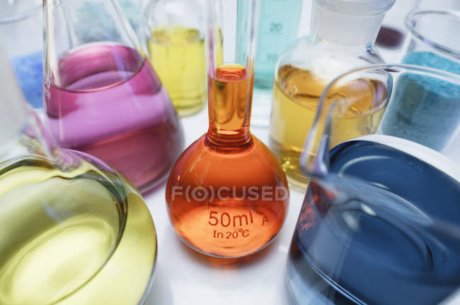 Volumetric flask containing solution of potassium dichromate and other flasks of transition metal salts — Stock Photo