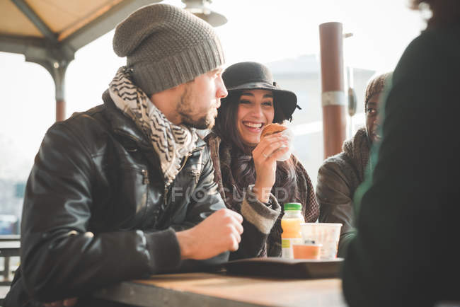 Four young adult friends chatting and eating doughnuts at sidewalk cafe — Stock Photo