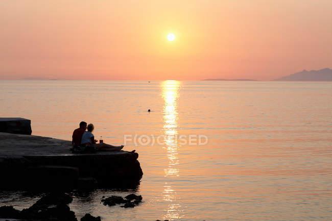 Пара відпочиваючи на пірсі на заході сонця — стокове фото