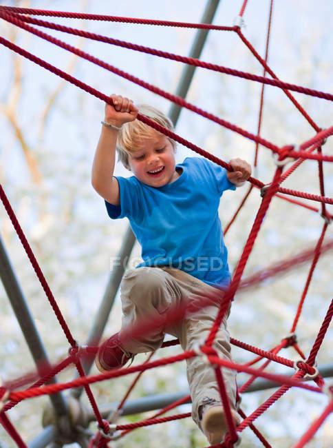 Garçon grimpant à l'aire de jeux — Photo de stock