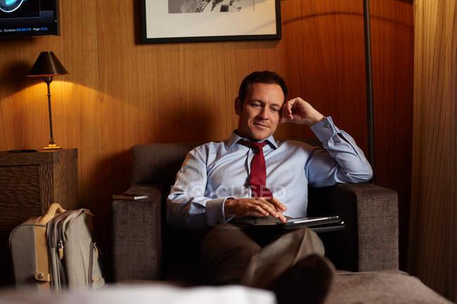 Empresario usando tableta en habitación de hotel - foto de stock