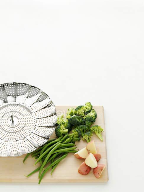 Verduras y patatas con colador en la tabla de cortar - foto de stock