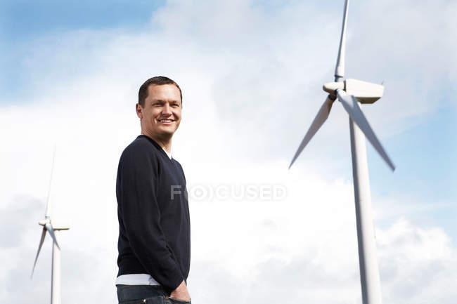 Sorrindo homem de pé no parque eólico — Fotografia de Stock
