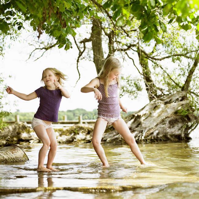 Smiling girls playing in lake, selective focus — Stock Photo