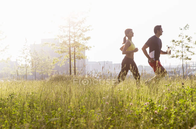Side view of Couple jogging in park — Stock Photo