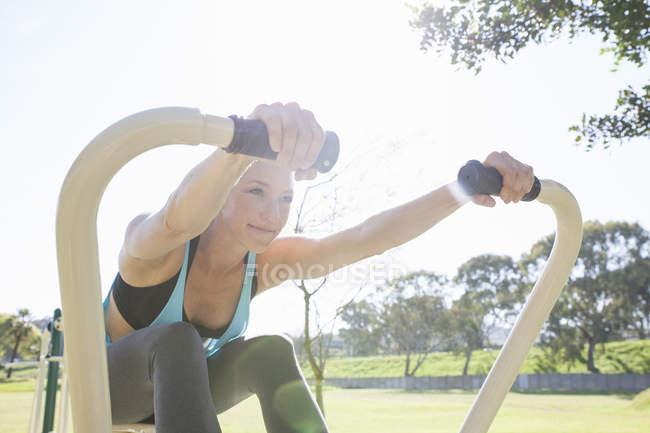 Средняя взрослая женщина тренируется на гребной машине в парке — стоковое фото