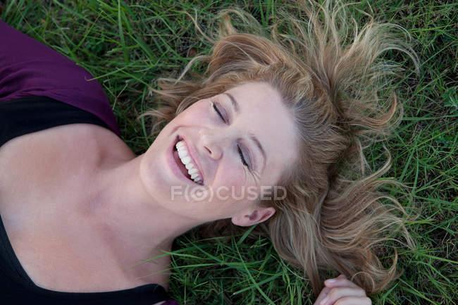 Улыбающаяся женщина лежит в траве — стоковое фото