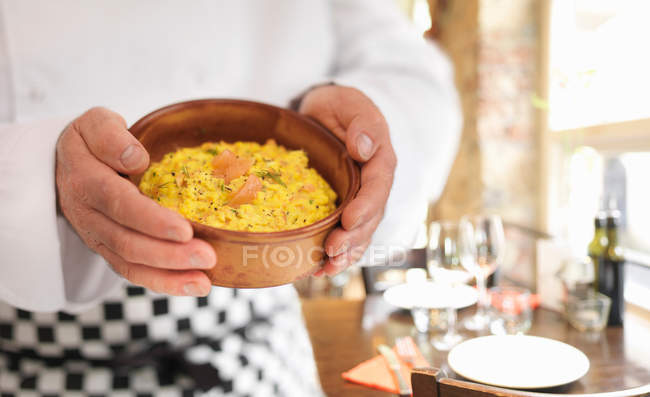 Chef holding eggs and salmon in bowl — Stock Photo