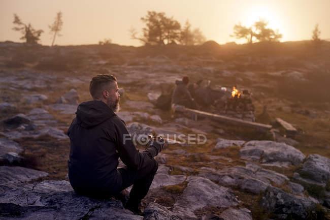 Escursionista rilassante con caffè sul campo roccioso, Sarkitunturi, Lapponia, Finlandia — Foto stock
