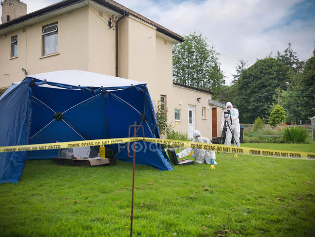 Forensic scientists outside house at crime scene, police tape in foreground — Stock Photo
