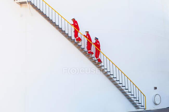 Trabajadores en las escaleras de la planta química - foto de stock