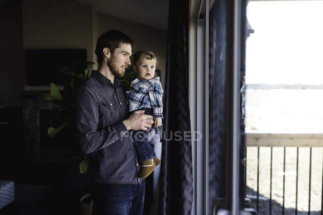 Людина і малюк син дивиться на вікна будинку — стокове фото