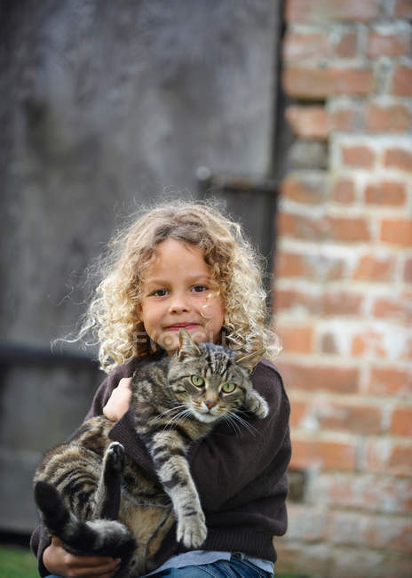 Young girl holding pet cat outside — Stock Photo