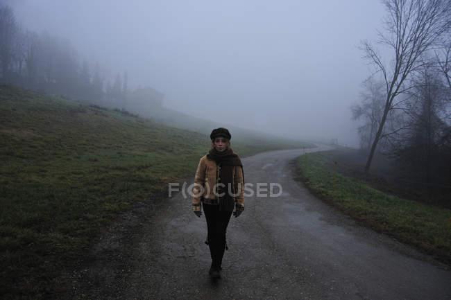 Woman walking on foggy rural road — Stock Photo