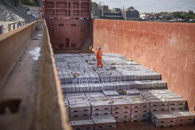 Operaio in piedi su lingotti di metallo nella stiva della nave — Foto stock